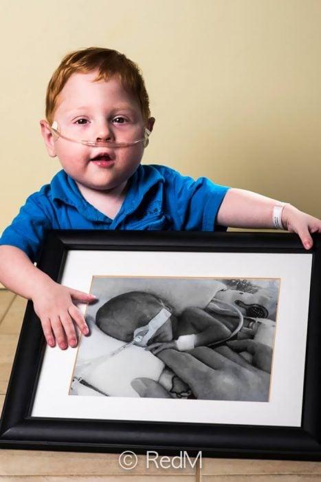 niño sosteniendo un cuadro de él mismo cuando era un bebé prematuro