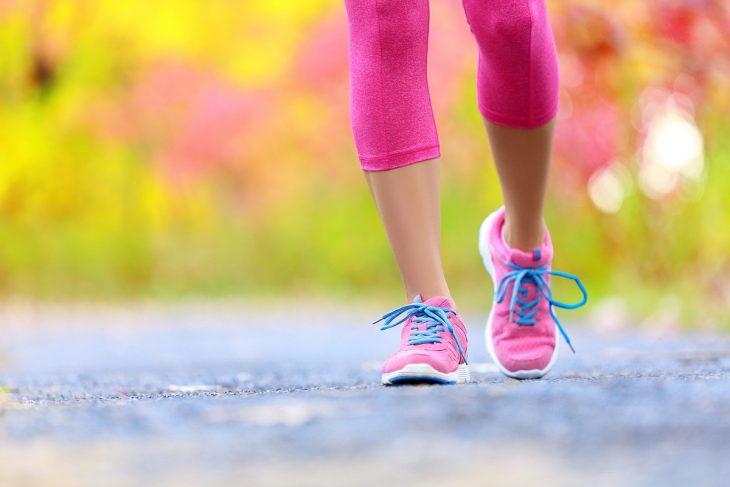 mujer caminando con tenis rosa