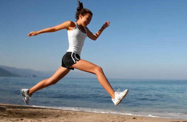mujer contenta saltando en la playa