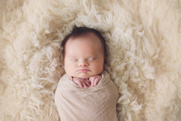 sesión de fotos de una bebé que nació con un tumor en el cerebro y síndrome de down recostada en una cama