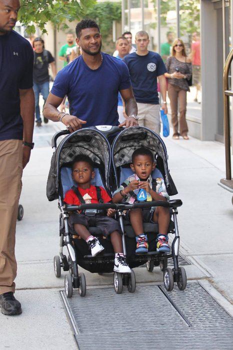 Usher con sus hijos de paseo en carreola