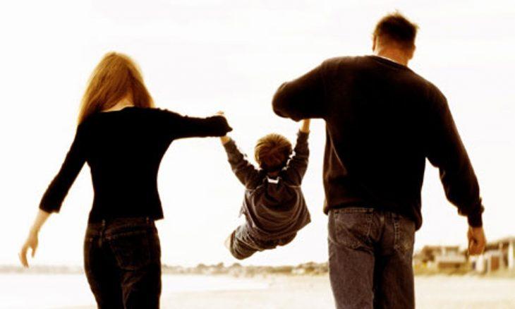 padres alzando en brazos a hijo