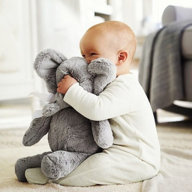 bebé jugando con peluche