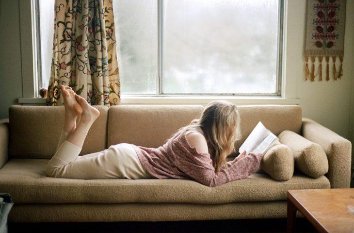 Chica recostada en un sofá leyendo un libro