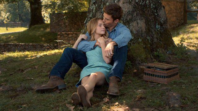 Pareja de novios recargados en un árbol y sentados en el suelo descansando