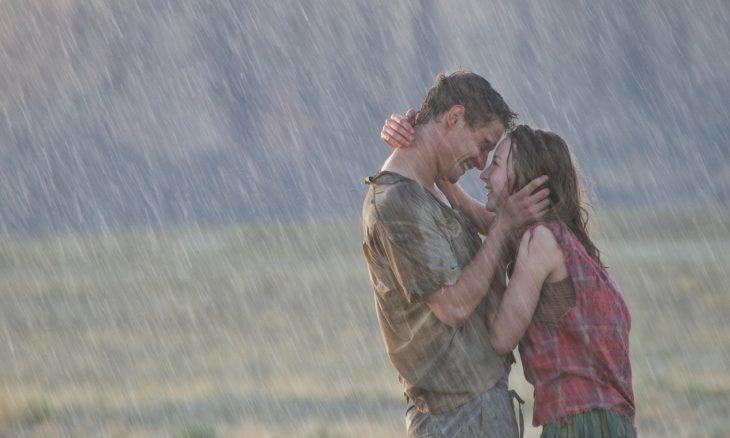 Pareja de novios besándose bajo la lluvia