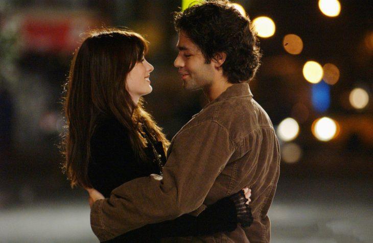 Escena de la película el diablo viste a la moda chica al lado de su novio abrazados