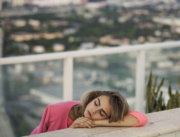 Cara Delavinge dormida sobre una tabla de madera