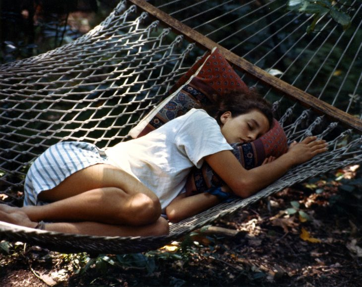 chica durmiendo en una hamaca en el jardín