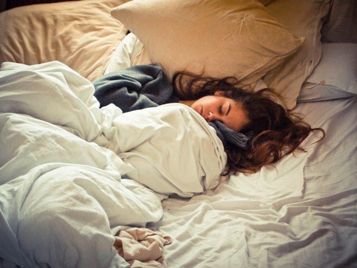 Chica con el cabello revuelto durmiendo en una cama