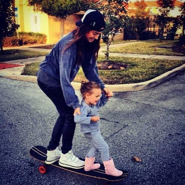 chica y niña pequeña en patineta