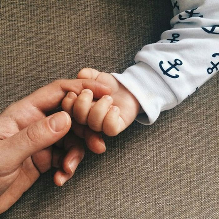 mano de mujer y bebé tocándose