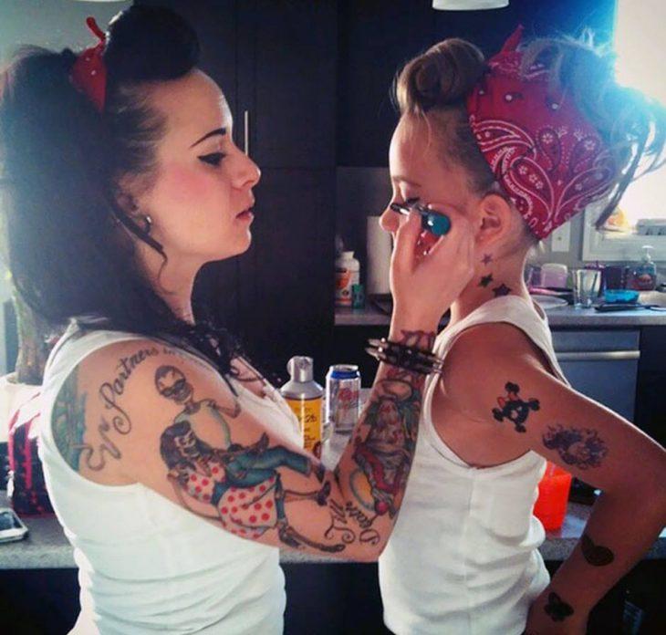 chica tatuada maquilla a niña pequeña
