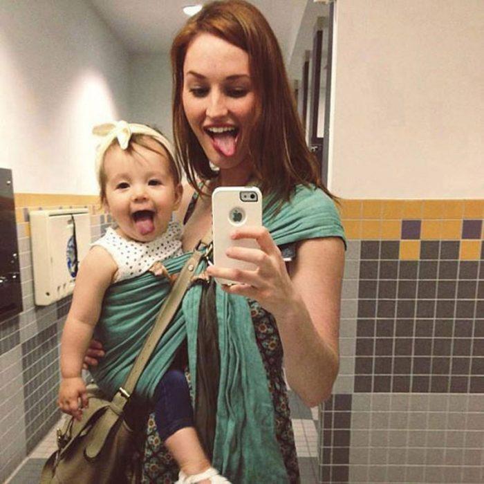 chica y bebé frente al espejo tomando selfie