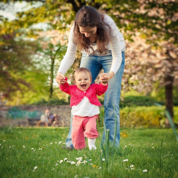 mujer enseña a caminar a bebé