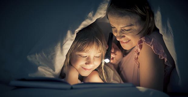 chica y niña leyendo a oscuras