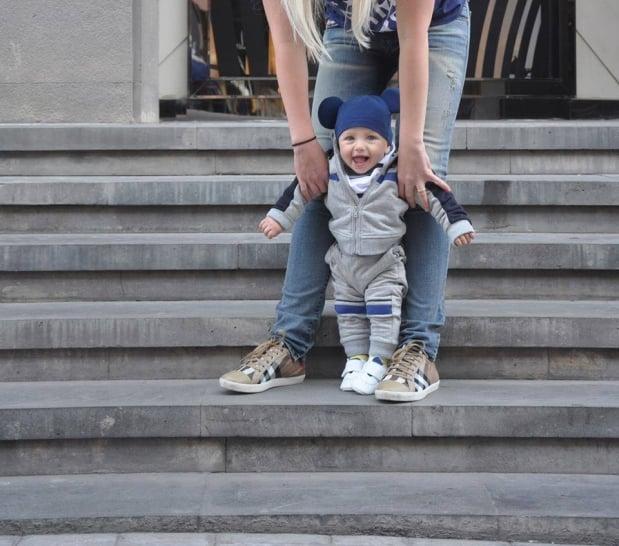 Chica sosteniendo a un bebé para que de sus primeros pasos