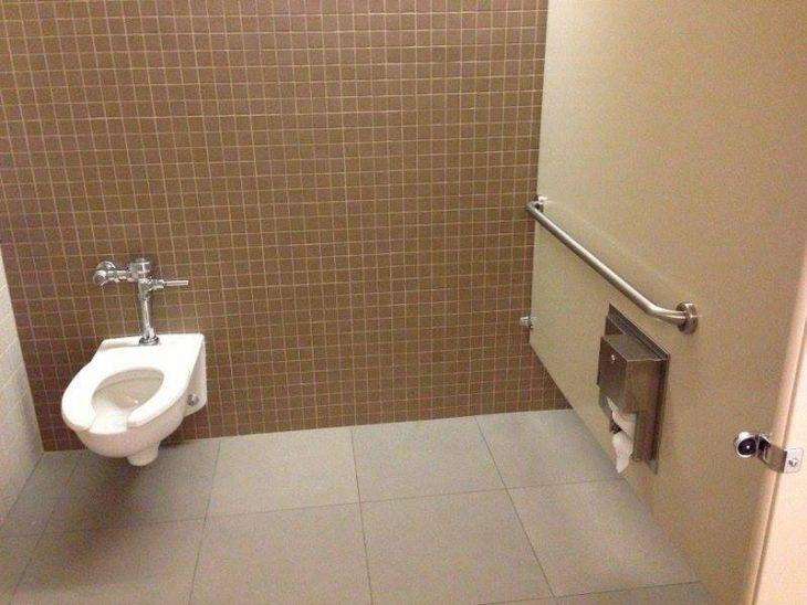 baño con tasa y dispensador de papel mal distribuídos