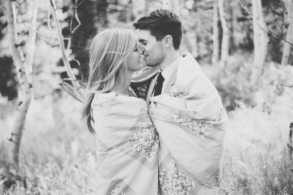Pareja de novios abrazados con una manta viéndose fijamente