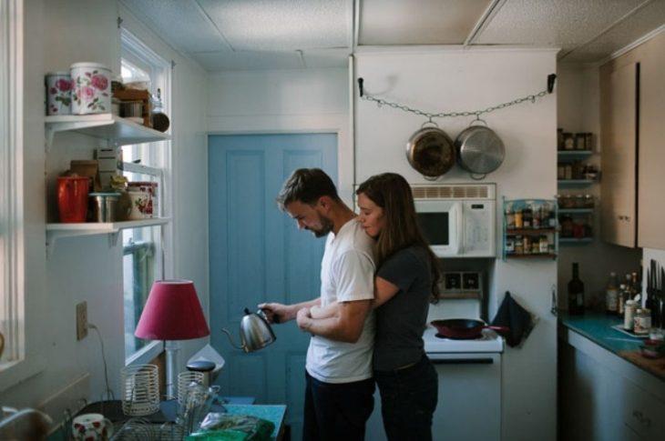 mujer abraza a hombre que está cocinando