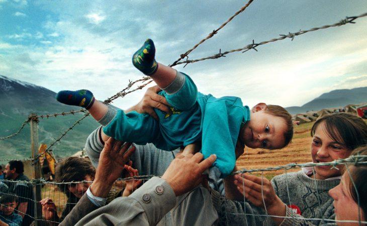 niño refugiado es pasado entre púas de alambre