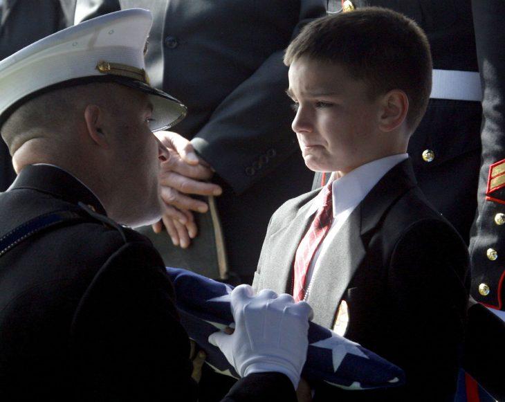 niño recibe la bandera de su padre muerto en Irak
