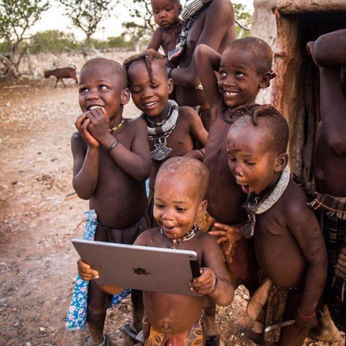 niños africanos sonríen al ver una tableta
