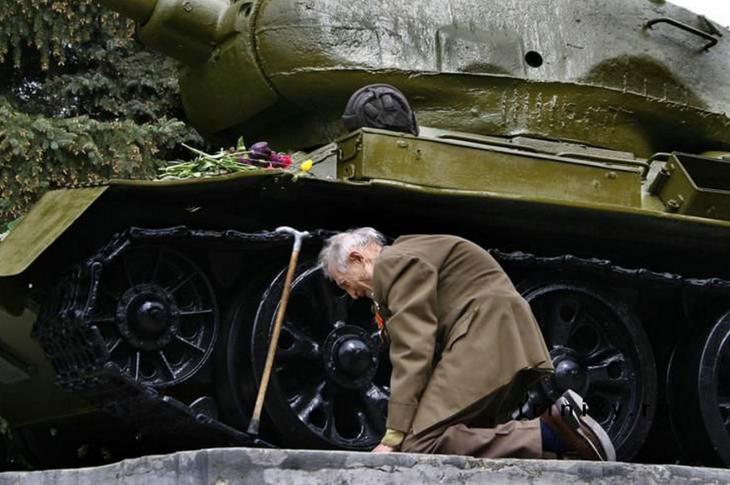 soldado ruso se arrodilla frente a tanque de guerra