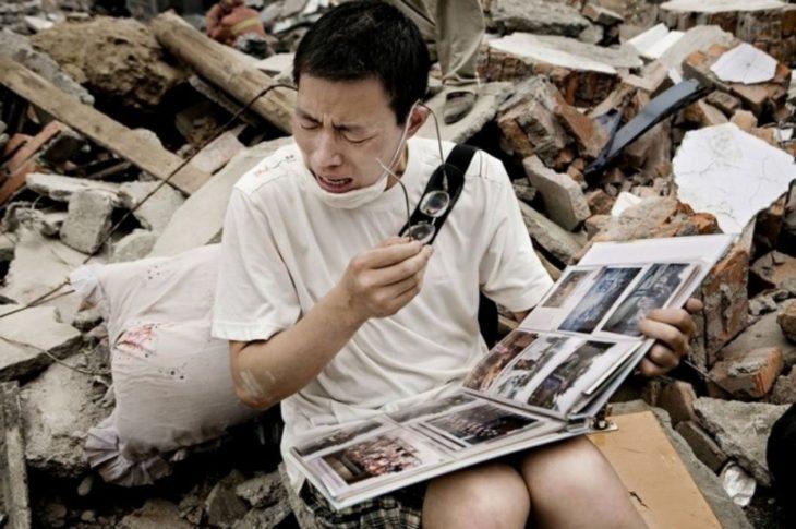 Hombre chino llora al ver album de fotos frente a las ruinas de su casa