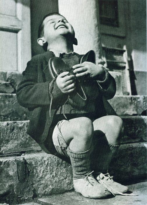 niño contento recibe zapatos nuevos
