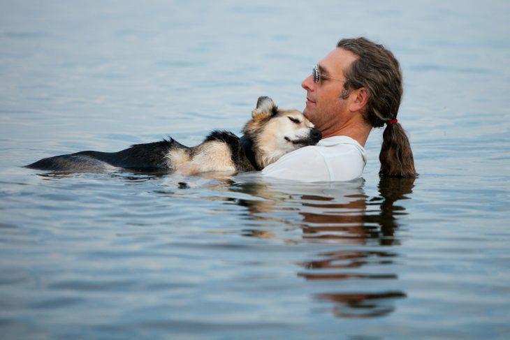 hombre baña a su perro artrítico en lago
