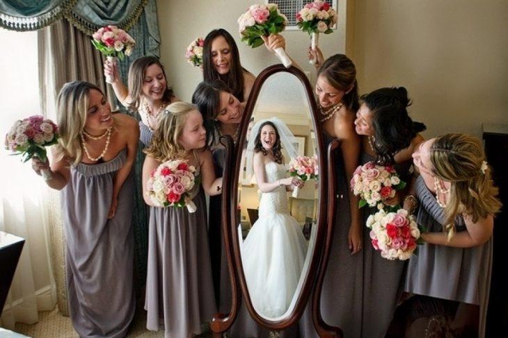 novia se refleja en espejo rodeado de damas