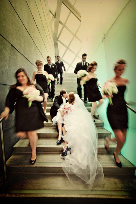 novios al centro y damas en movimiento bajando escalers