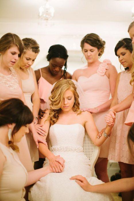 damas orando alrededor de la novia