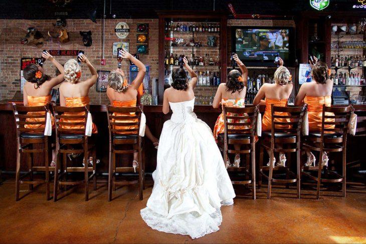 novia y damas de espaldas sentadas frente a la barra de un bar