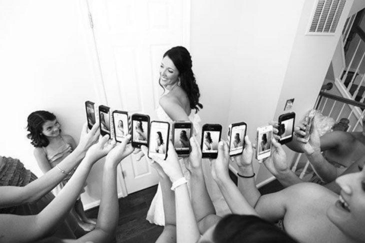 damas tomando fotografía a novia con sus celulares