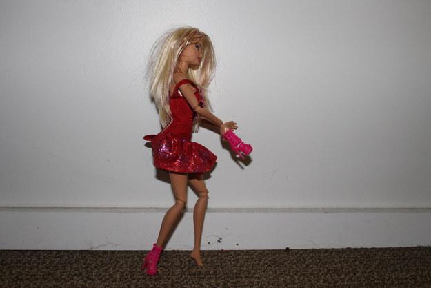 Barbie caminando con un zapato en la mano