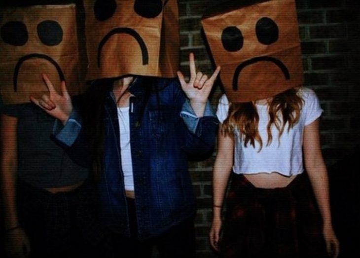 jóvenes con bolsas de papel en la cara