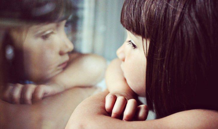 niña mirando su reflejo por la ventana