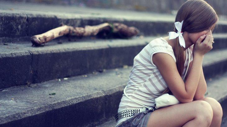 chica triste sentada en la escalera