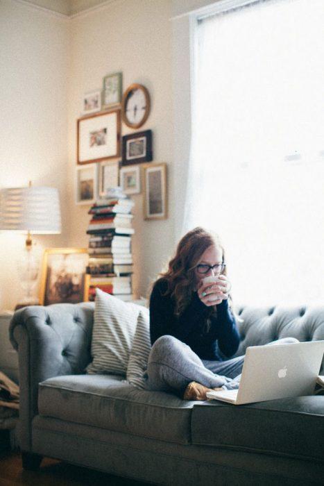 Chica bebiendo café mientras trabaja con su laptop en el sofá