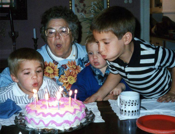 Niños soplando una vela de un pastel de cumpleaños