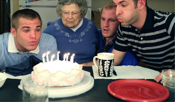 Hombres soplando una vela de cumpleaños en un pastel acompañados de su abuela