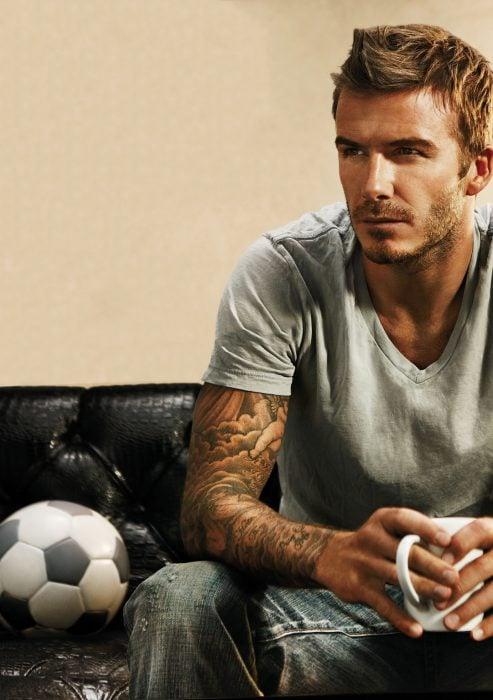 david beckham sentado en un sofá bebiendo café