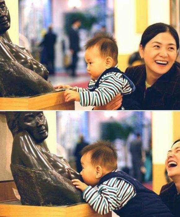 Niño tomando el pecho de una estatua