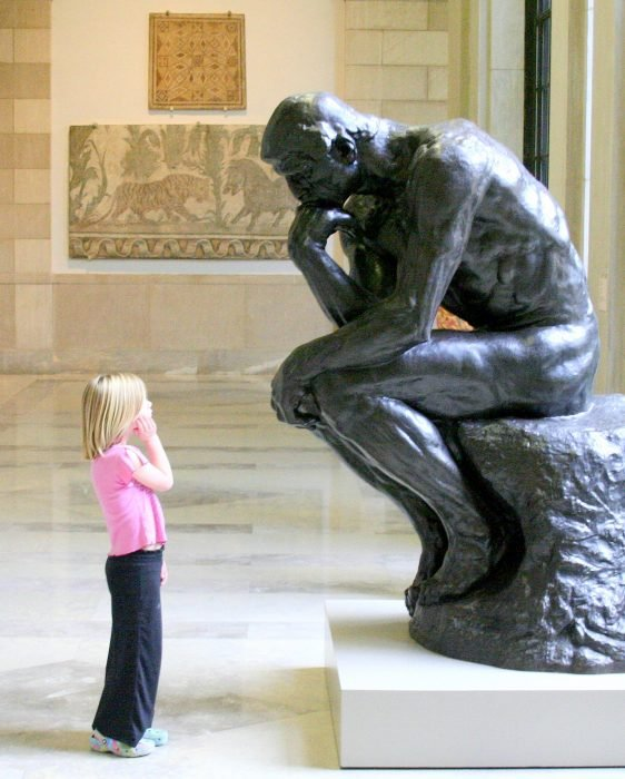 Niña mirando fijamente a una estatua