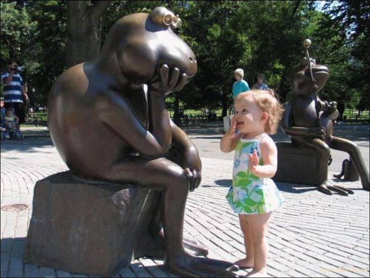 Niña viendo con una mano en la boca a una estatua en forma de rana