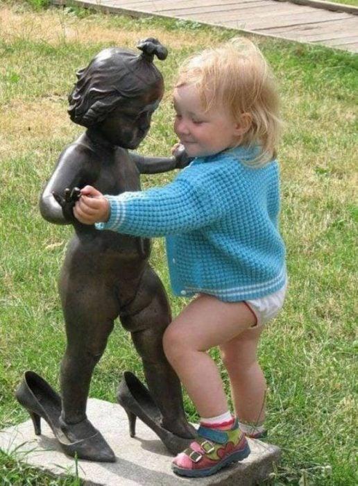 Niña intentando bailar con una estatua en forma de niña