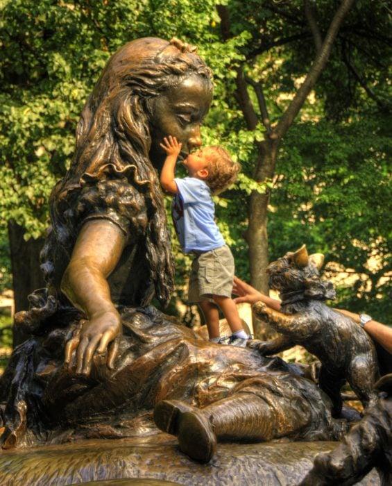 Niño besando a una estatua en la boca