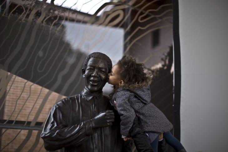 Niño besando a una estatua en forma de señor
